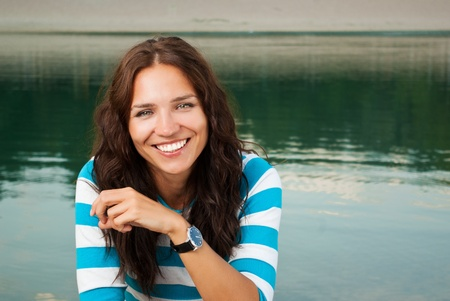 retouched: Portrait of young beautiful smiling female near the lake