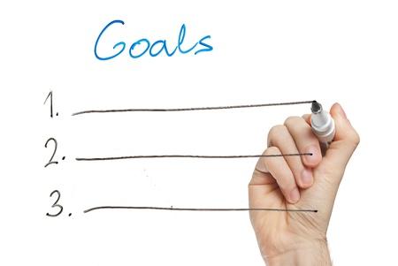 metas: mano escribiendo objetivos en pizarra Foto de archivo