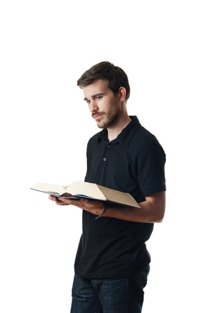 Attractive young man reading a book isolated on white photo