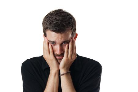 caras tristes: Malestar hombre preocupado joven con la cara entre las manos entrelazadas y la cabeza inclinada aislado en blanco