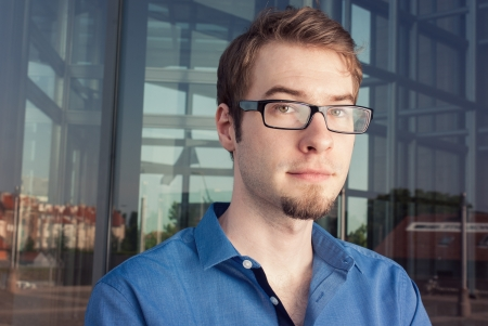 attractive young businessman with glasses in front of modern building photo