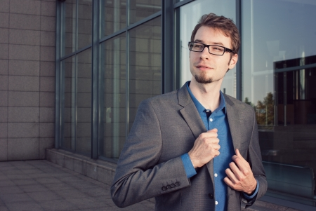 attractive young businessman looking satisfied with work in front of modern office building photo