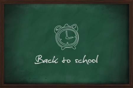 Back to school with alarm clock on chalkboard photo