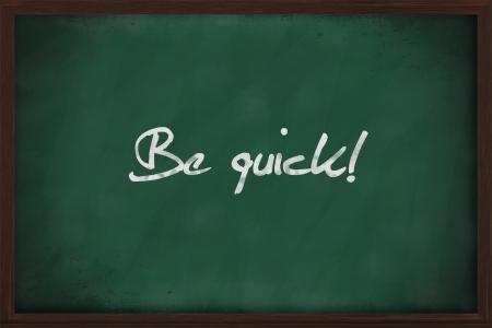 short phrase: Be quick written on a green chalkboard