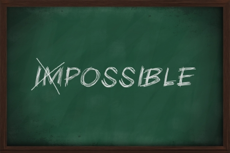 Turning the word Impossible into Possible on chalkboard photo
