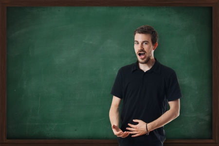 Young attractive music teacher singing in front of chalkboard photo