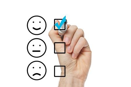 Hand zetten vinkje met blauwe markering op klantenservice evaluatieformulier Stockfoto