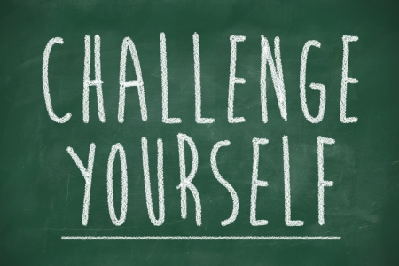 challenge yourself phrase handwritten on school blackboard photo