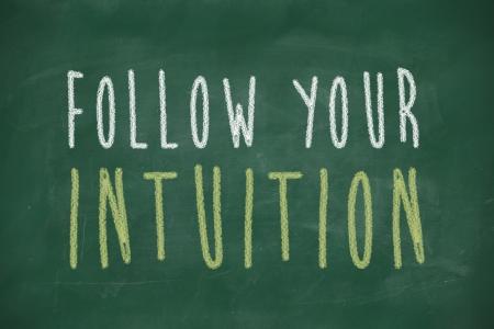 phrase: follow your intuition phrase handwritten on blackboard Stock Photo