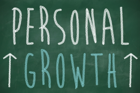 personal goals: Personal growth phrase handwritten on the chalkboard with rising arrows