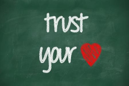 trust your heart phrase handwritten on blackboard with chalk photo