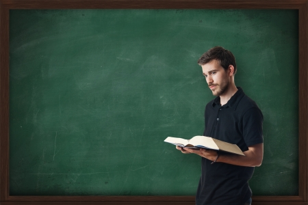 Young professor teaching in front of a blackboard photo