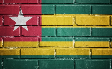 Togo flag on texture brick wall photo