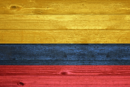 Colombia Flag painted on old wood plank background photo