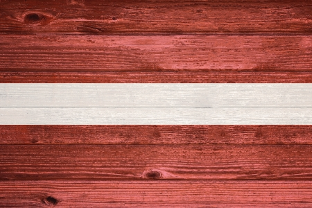 Latvia Flag painted on old wood plank background photo