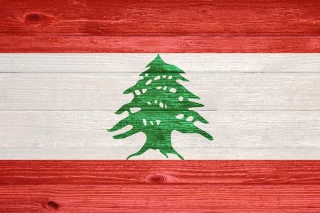 Lebanon Flag painted on old wood plank background photo