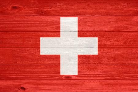 Switzerland Flag painted on old wood plank background photo