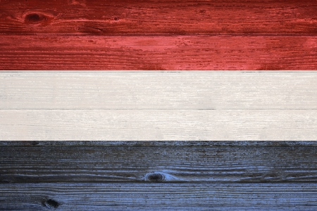 The Netherlands Flag painted on old wood plank background photo