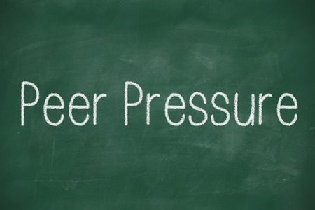 peer pressure: Green chalk board with the white words peer pressure written on it