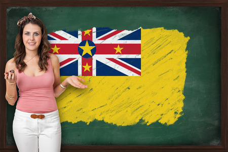 niue: Beautiful and smiling woman showing flag of Niue on blackboard