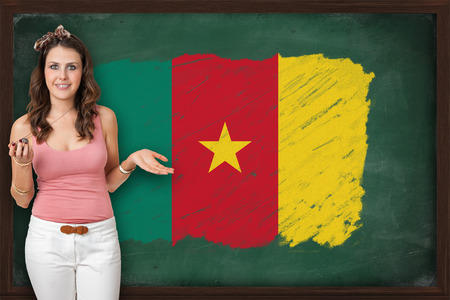 Beautiful and smiling woman showing flag of Cameroon on blackboard