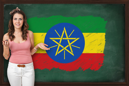 Beautiful and smiling woman showing flag of Ethiopia on blackboard photo