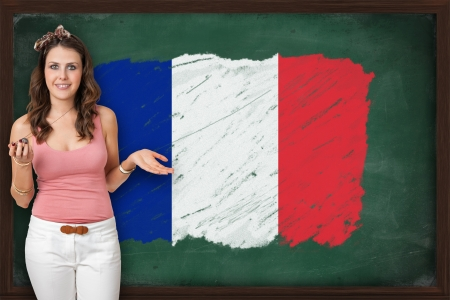 Beautiful and smiling woman showing flag of France on blackboard photo
