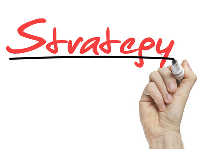 Hand writing strategy on a white board - business concept photo