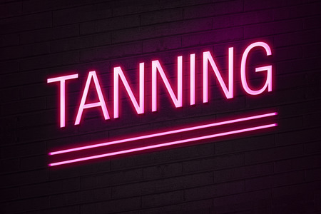suntan: Pink neon sign with tanning text on wall