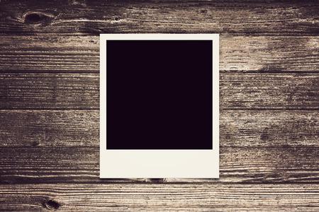one Polaroid retro frame on wood texture nostalgic vintage look
