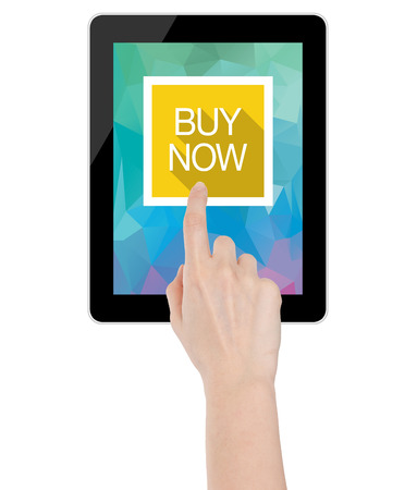 Female hand touching a buy now icon on a tablet computer with geometric polygon triangle wallpaper photo