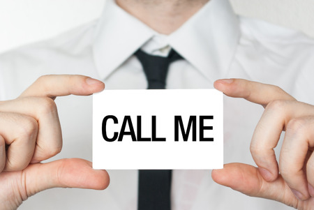 Call me. Businessman in white shirt with a black tie showing or holding business card photo