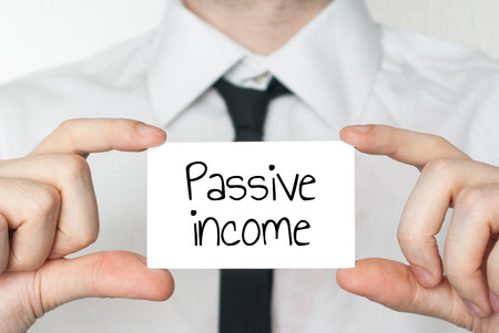passive: Businessman holding or showing card with text passive income