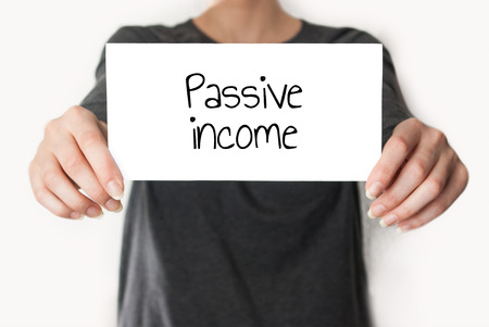 Girl holding or showing card with text passive income photo