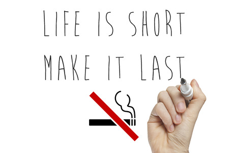 crossed cigarette: Hand writing life is short make it last on a white board with cigarette crossed Stock Photo