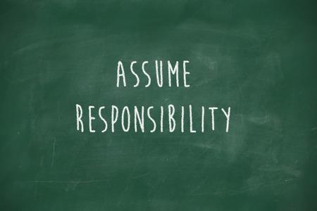 assume: Assume responsibility handwritten on school blackboard