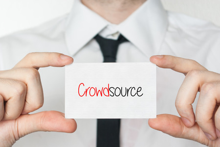 crowdsource: Crowdsource. Businessman in white shirt with a black tie showing or holding business card  Stock Photo