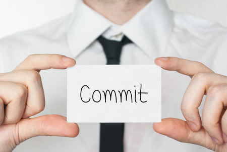 to commit: Commit. Businessman in white shirt with a black tie showing or holding business card