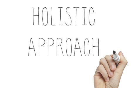 Escritura de la mano enfoque holístico en un tablero blanco