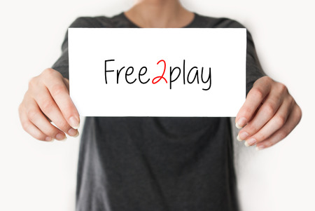 Free2play. Female in black shirt showing or holding a card photo