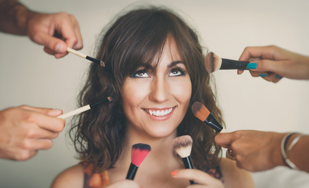 maquillaje de ojos: Concepto de la belleza con la cara de una hermosa mujer joven rodeada de estilistas manos la celebraci�n de una gran variedad de cosm�ticos y pinceles de maquillaje y aplicadores Foto de archivo