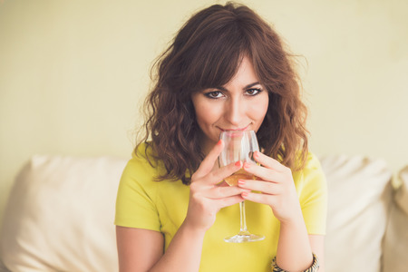 Thoughtful attractive young woman drinking a glass of champagne or white staring pensively down at the floor wine photo
