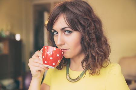 inscrutable: Close Up of Woman Drinking from Red Polka Dot Tea Mug and Looking at Camera Stock Photo