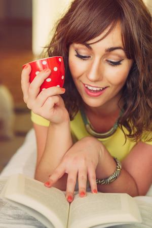 mujer leyendo libro: Mujer sonriente miente en el estómago y mantiene la taza mientras que Reading Paperback Book