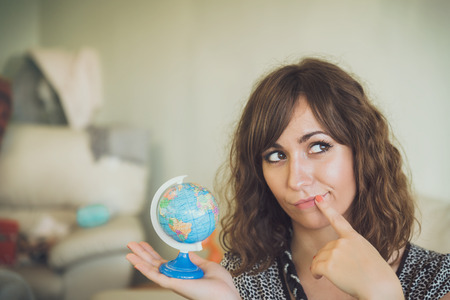 Thinking Woman Holding Small Globe in Hand as if Deciding Where to Travel