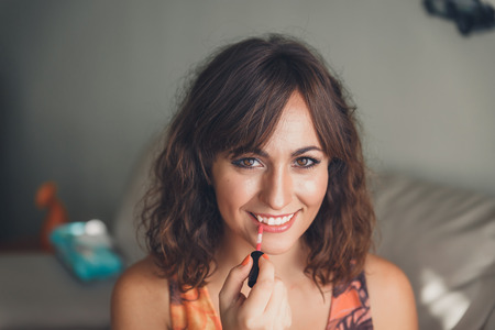 applying lipstick: Attractive young woman with curly brunette hair applying her lipstick smiling at camera in a fashion and beauty concept