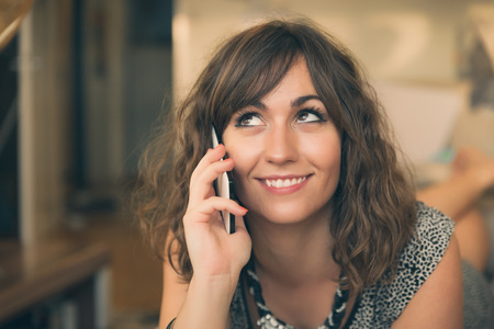 Close Up Portrait of Smiling Brunette Woman Talking on Cell Phone photo