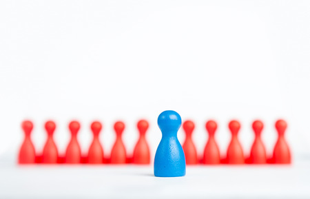 Stand out and be unique - leadership business concept with game figurines on white photo