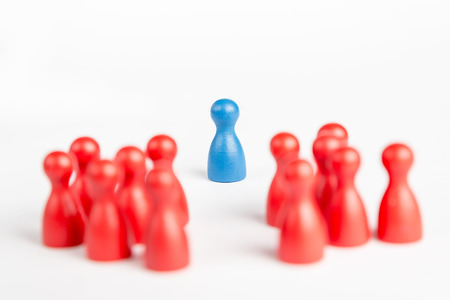 praised: Center of attention blue pawn surrounded and praised by red pawns Stock Photo
