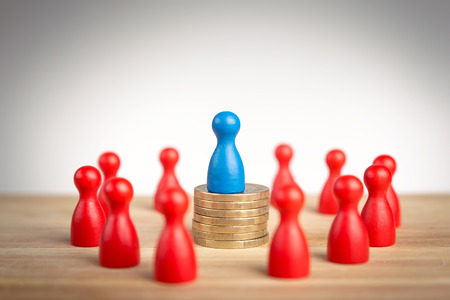 wealth concept: Rich business leader concept with blue figure on top of coin stack as a symbol of wealth Stock Photo